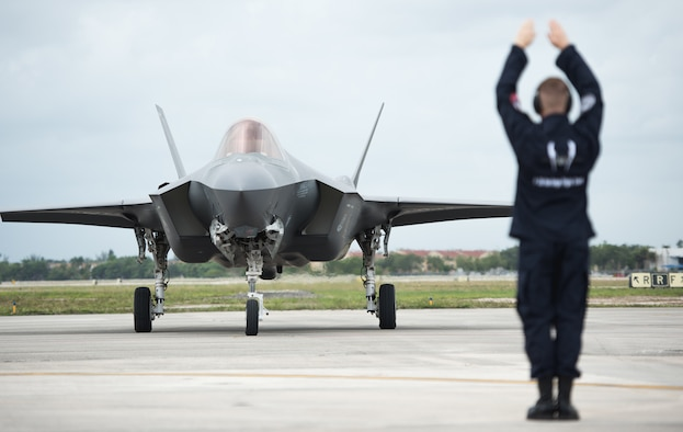 Staff Sgt. Michael Couture, F-35 Heritage Flight Team crew chief, marshals an F-35A Lightning II upon arrival at the Miami-Opa Locka Executive Airport in Opa-Locka, Fla., May 24, 2018. The F-35 HFT arrived in Miami to perform at the 2018 Hyundai Air and Sea show; a two-day event held during Memorial Day weekend to honor military service members. (U.S. Air Force photo by Airman 1st Class Alexander Cook)