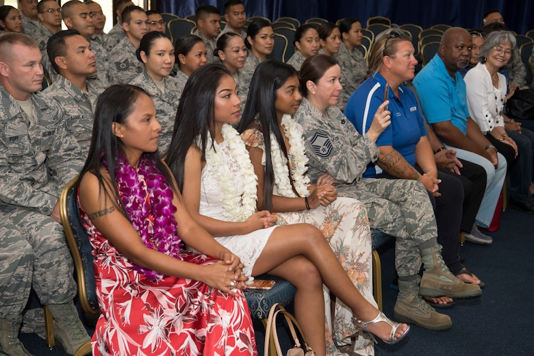 The family of U.S. Air Force Lt. Col. Carla Lugo, which include her wife, Tricia Topasna (left) along with their children, Asia Topasna, Sadie Topasna, and via video conference her Emilio Tullie and Stephanie Delgado attend her assumption of command of the 44th Aerial Port Squadron during a ceremony at Andersen Air Force Base, Guam, June 2, 2018, where Lugo became the squadron commander.