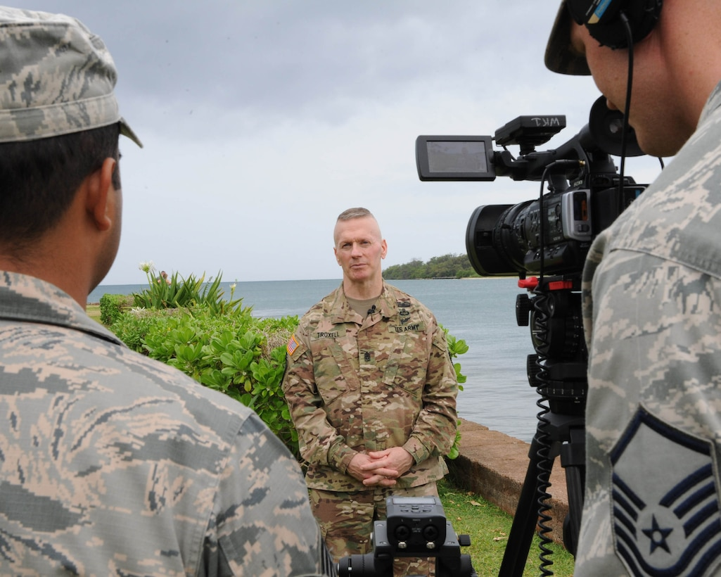 U.S. Air Force Staff Sgt. Daniel Robles (left) and Master Sgt. George Maddon (right), Pacific Air Forces broadcast journalists, interview U.S. Army Command Sgt. Maj. John Wayne Troxell, senior enlisted advisor to the chairman of the Joint Chiefs of Staff, during an enlisted all-call at Joint Base Pearl Harbor-Hickam, Hawaii, May 29, 2018. Troxell is the designated senior noncommissioned officer in the U.S. armed forces and advises the Chairman and the Secretary of Defense on all matters involving joint and combined total force integration, utilization, health of the force, and joint development for enlisted personnel. (U.S. Air Force photo by Master Sgt. Taylor Worley)