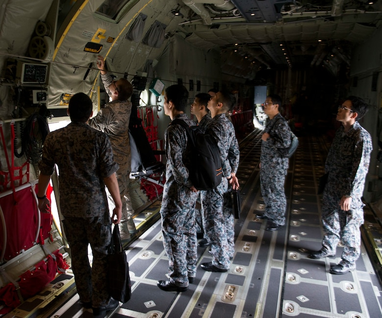 U.S. Air Force Airman 1st Class Joseph Totin, 374th Maintenance Squadron crew chief, shows Koku-Jieitai Airmen the capabilities of a C-130J Super Hercules