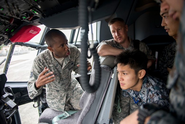 Staff Sgt. Ennis Mayberry, 374th Maintenance Squadron crew chief, talks about the C-130J Super Hercules with Koku-Jieitai maintenance officers