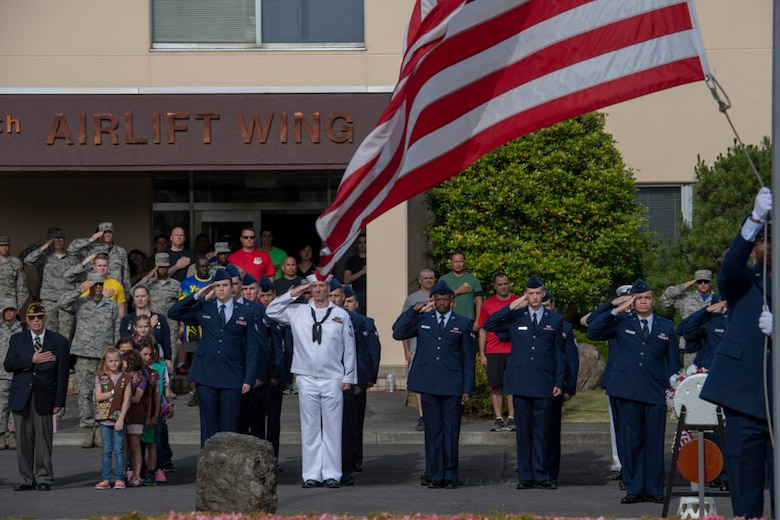 Service members salute during a ceremony for Memorial Day at Yokota Air Base