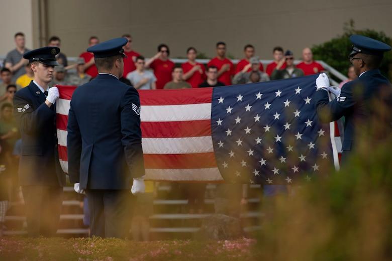 Yokota honor guardsmen fold an American flag during the Memorial Day ceremony
