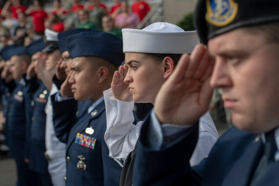 Service members salute during a ceremony for Memorial Day