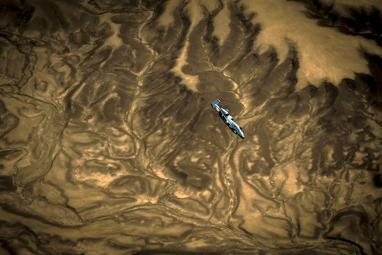 An aircraft flies over dramatic brown and tan terrain swirling that appears marbled.