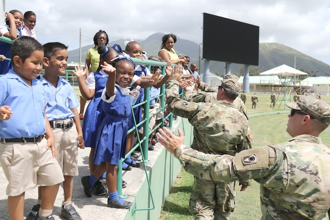 U.S. Army National Guard Soldiers greet school children.