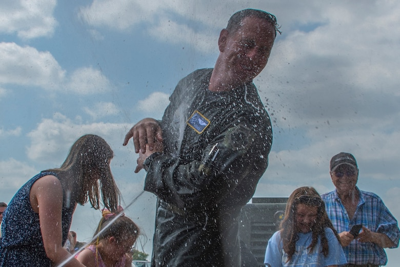 U.S. Air Force Col. Christopher Anderson, vice commander of the 307th Bomb Wing, tries to avoid being sprayed with water by family and friends at Barksdale Air Force Base, Louisiana, June 1, 2018. Anderson had just completed his 'fini flight' which is a military aviator's last flight with his assigned unit or before retirement from the service. (U.S. Air Force photo by Airman Maxwell Daigle/Released)