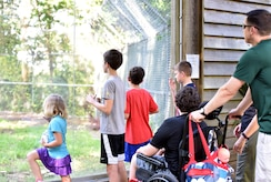 Lt. Col. Bryan Collins, 628th Comptroller Squadron commander, and his family look into the cage of red wolves during an Exceptional Family Member Program event June 1, 2018, at the Charles Town Landing Zoo.