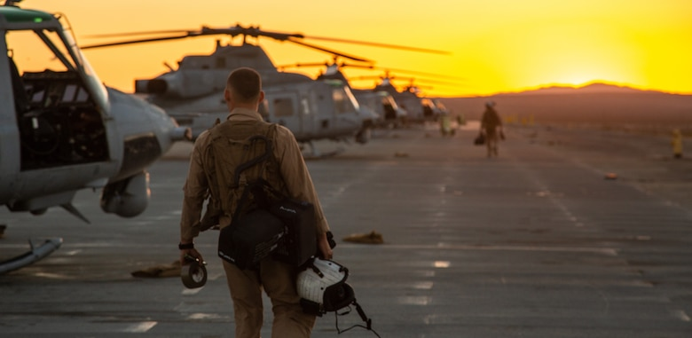 A pilot with Light Attack Helicopter Squadron 367, also known as 'Scarface', heads toward the UH-1Y Venom Utility helicopters for a nighttime flight mission during the Final Exercise of Integrated Training Exercise 3-18 aboard the Marine Corps Air Ground Combat Center, Twentynine Palms, Calif., May 23, 2018. Marine aviation provides the Marines of the Marine Air Ground Task Force the operational flexibility it needs to accomplish their mission. (U.S. Marine Corps photo by Lance Cpl. Dave Flores)