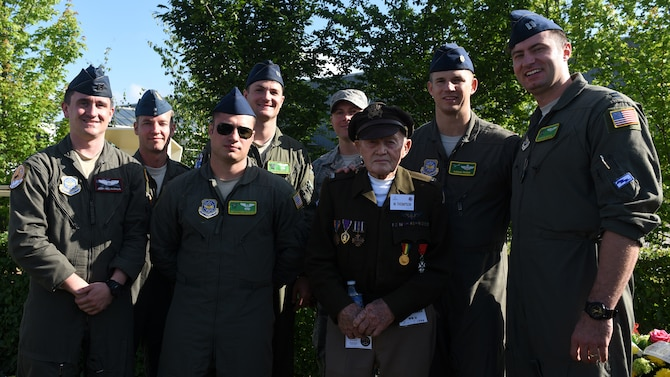 Pilots pose in flight suits for photo along side World War 2 D-Day survivor wearing world war 2 uniform and bomber jacket.