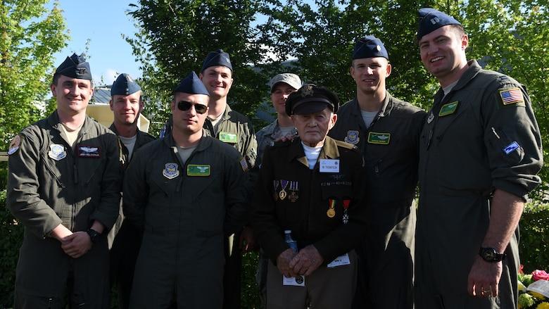 Pilots pose in flight suits for photo along side World War 2 D-Day survivor wearing world war 2 uniform and bomber jacket.
