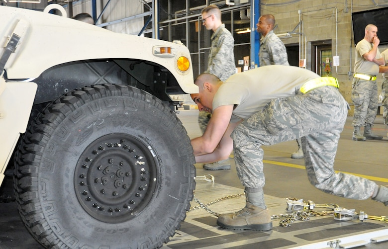 Tech. Sgt. Eric Wadlington, 87th Aerial Port Squadron special handling technician, works to quickly attach a chain to the tie-down point of a Humvee, simulating how a vehicle must be secured to the floor of an aircraft May 5, 2018. Wadlington was one of several team members working to secure the vehicle as judges observed for safety violations and technical errors during the Port Dawg Challenge May 5, 2018.