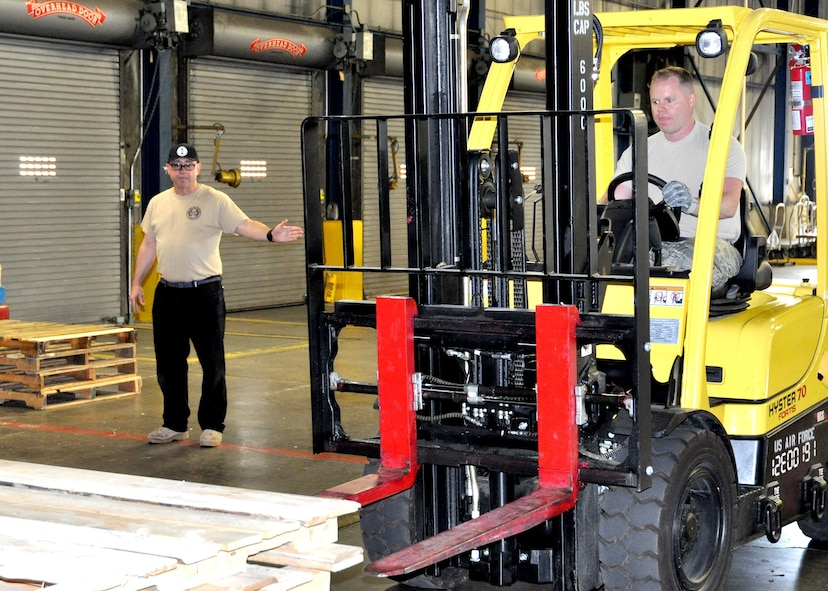 Retired Tech. Sgt. Larry Moorman, provides instruction as Senior Master Sgt. Nathan Livingston maneuvers an indoor forklift May 5, 2018. More than 100 members of the 87th Aerial Port Squadron competed in small teams against one another to earn the highest honors during the Port Dawg Challenge.