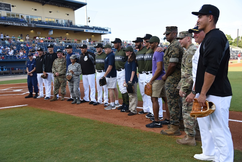 Local military members pose for a group photo with Shuckers baseball players during the Biloxi Shuckers Minor League Baseball team's military appreciation night at MGM Park in Biloxi, Mississippi, June 2, 2018. The Shuckers recognized and honored service members and their families for the dedication, commitment and sacrifices they make for the nation. (U.S. Air Force photo by Kemberly Groue)