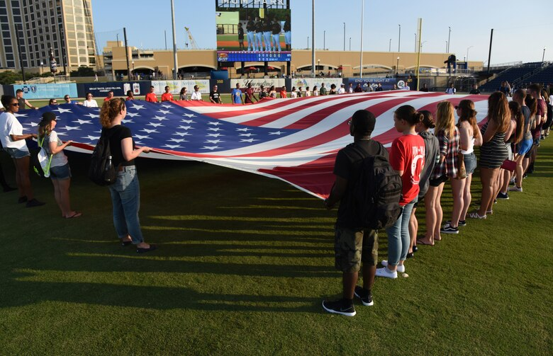 Airmen from the 81st Training Group hold the U.S. flag during the Biloxi Shuckers Minor League Baseball team's military appreciation night at MGM Park in Biloxi, Mississippi, June 2, 2018. Keesler Airmen and leadership also participated in pre-game festivities that included presenting the colors, flag display and throwing the ceremonial first pitches. (U.S. Air Force photo by Kemberly Groue)