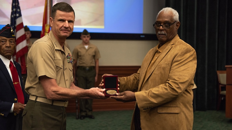 Lt. Gen. William D. Beydler, commander of Marine Corps Force Central Command, presents Clement E. Hill with the Congressional Gold Medal in honor of his late father Pfc. Burnie W. Hill, May 31, 2018 at MacDill Air Force Base, Florida. In 1942, African Americans were given the opportunity to enlist in the United States Marine Corps. Nearly 20,000 African Americans from 1942-1949 were trained separately from their white counterparts at Montford Point, a facility at Camp Lejeune, North Carolina.