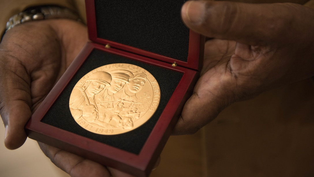 Clement E. Hill holds the Congressional Gold Medal posthumously awarded to his father Pfc. Burnie W. Hill, a Montford Point Marine May 31, 2018 at MacDill Air Force Base, Florida. In 1942, African Americans were given the opportunity to enlist in the United States Marine Corps. Nearly 20,000 African Americans from 1942-1949 were trained separately from their white counterparts at Montford Point, a facility at Camp Lejeune, North Carolina.