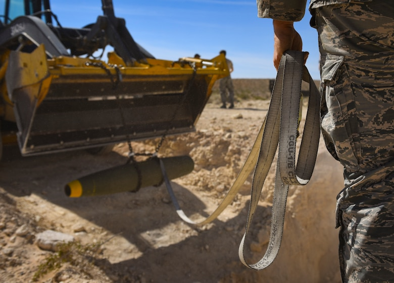 Tech. Sgt. Robert Brousseau, 99th Civil Engineer Squadron explosive ordnance disposal technician, uses a strap to guide a Mark 82 bomb during an ammunition disposition request at Nellis Air Force Base, Nevada, May 31, 2018. EOD technicians buried the 500-pound Mark 82 bomb underground and then covered it with dirt to minimize the blast radius of fragmentation and debris. (U.S. Air Force photo by Airman 1st Class Andrew D. Sarver)