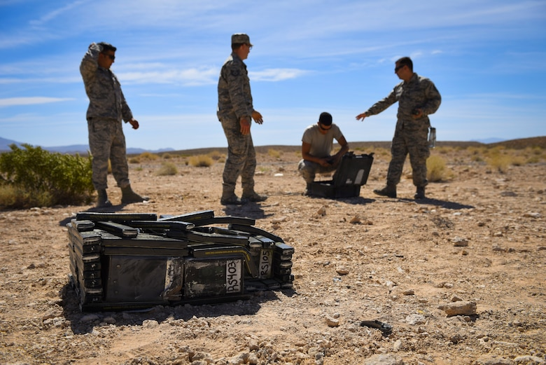 99th Civil Engineer Squadron explosive ordnance disposal technicians prepare a crate of flares for detonation during an ammunition disposition request at Nellis Air Force Base, Nevada, May 31, 2018. EOD technicians placed C4 around the crate to ensure every component was completely destroyed. (U.S. Air Force photo by Airman 1st Class Andrew D. Sarver)