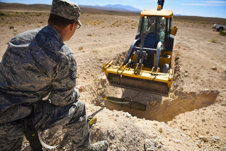 Tech. Sgt. Robert Brousseau, 99th Civil Engineer Squadron explosive ordnance disposal technician, guides a Mark 82 bomb into a hole during an ammunition disposition request at Nellis Air Force Base, Nevada, May 31, 2018. EOD technicians buried the 500-pound Mark 82 bomb underground and then covered it with dirt to minimize the blast radius of fragmentation and debris. (U.S. Air Force photo by Airman 1st Class Andrew D. Sarver)