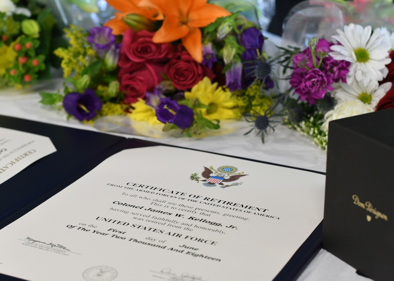 The certificate of retirement for James Kellogg, Jr., 94th Airlift Wing vice commander, sits on a presentation table flanked by flowers and a gift at Dobbins Air Reserve Base, Ga, June 2, 2018. The certificate was presented to the newly retired vice commander during his retirement ceremony, marking the end of a 30-year career in the Air Force. (U.S. Air Force photo by Staff Sgt. Miles Wilson)