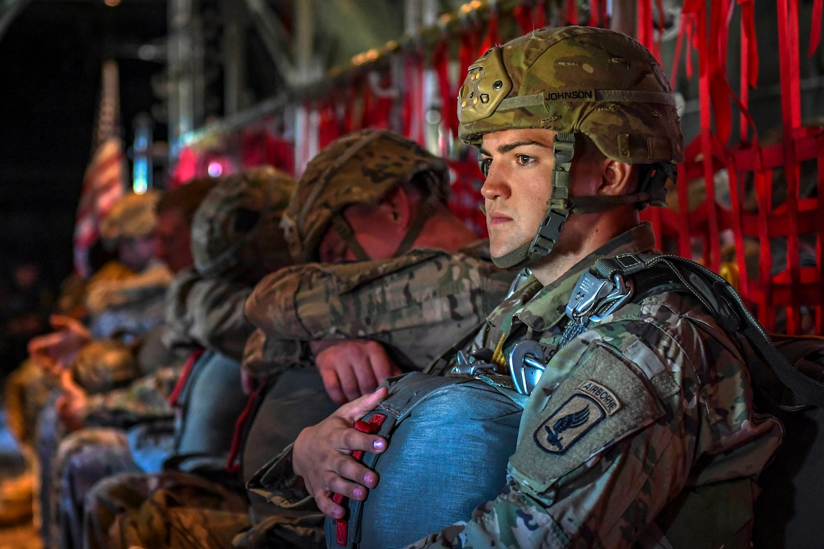 A soldier sits inside an aircraft with fellow troops and holds a parachute.