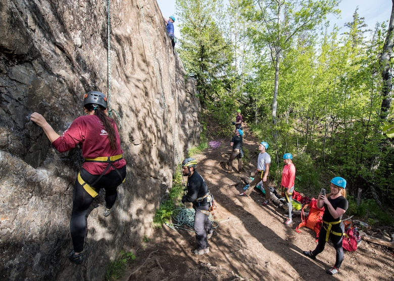 A group of climbers look on and cheer as two climbers in their group ascend during an Outdoor Adventure Program rock-climbing trip at Pivot Point Trail near Anchorage, Alaska, May 31, 2018. The OAP offers low-cost opportunities for the Joint Base Elmendorf-Richardson community to explore Alaska while also supporting the development of mission-ready military families and members.