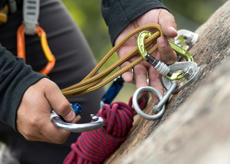 Christian Ortega, an Outdoor Adventure Program recreational assistant, ties off climbing rope with carabiners during the set-up of an OAP rock-climbing trip at Pivot Point Trail near Anchorage, Alaska, May 31, 2018. Ortega has been climbing for more than five years and has an internship with OAP on guided events and classes. The OAP offers low-cost opportunities for the Joint Base Elmendorf-Richardson community to explore Alaska while also supporting the development of mission-ready military members.