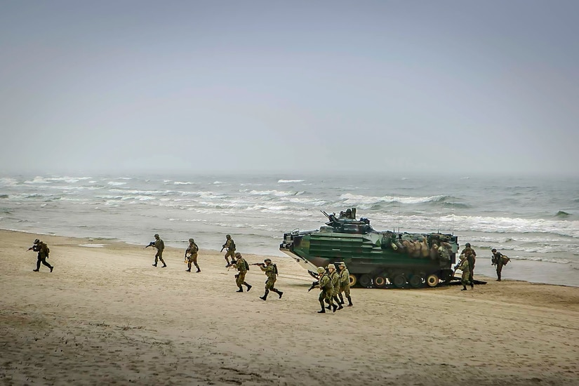 Troops point weapons while running on a beach away from a parked amphibious vehicle.