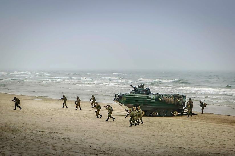 Les troupes pointent les armes en courant sur une plage, à l'écart d'un véhicule amphibie garé.