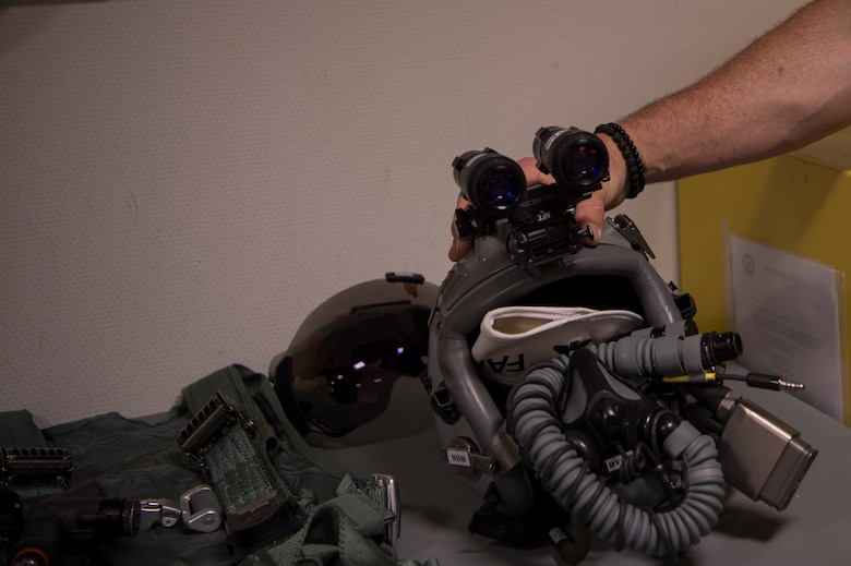 A pilot's F-16 helmet includes mounted night vision goggles that allow pilots to see in low light situations.