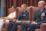 Three military officers sit on a stage in high-back chairs listening to a speaker during a change of command ceremony.