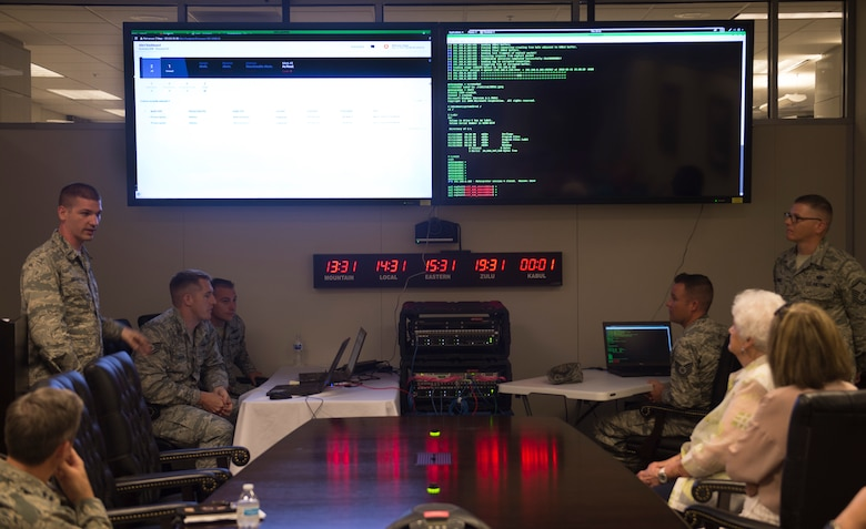 Airmen from the 836th Cyberspace Operations Squadron discuss defensive cyberspace operations during a civic leader tour at Joint Base San Antonio-Lackland, Texas, May 31, 2018. The civic leaders visited the base with Gen. Mike Holmes, commander Air Combat Command, to introduce them to 24th Air Force's cyberspace mission and 25th AF's intelligence, surveillance and reconnaissance mission. (U.S. Air Force photo by Tech. Sgt. R.J. Biermann)