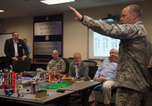 "Capt. Justin Ball, 390th Cyberspace Operations Squadron Weapons and Tactics chief, explains the purpose of the 90th Cyber Operations Squadron ""Bricks-in-the-Loop"" model to Gen. Mike Holmes, commander Air Combat Command, and civic leaders during a tour at Joint Base San Antonio-Lackland, Texas, May 31, 2018. The model is used as a cyber training tool to teach cyber Airmen information technology and operational technology network defense. The tour was hosted to introduce attendees to 24th Air Force's cyberspace mission and 25th AF's intelligence, surveillance and reconnaissance mission. (U.S. Air Force photo by Tech. Sgt. R.J. Biermann)"