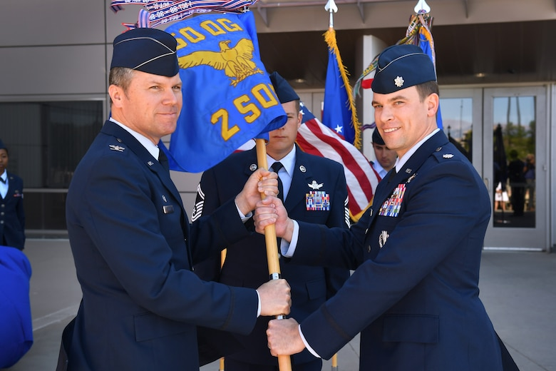 SCHRIEVER AIR FORCE BASE, Colo. – Col. Toby Doran, commander of the 50th Operations Group, passes the 2nd Space Operations Squadron guidon to Lt. Col. Stephen Toth, incoming commander of the 2nd SOPS, during a change of command ceremony at Schriever Air Force Base, Colorado, June 1, 2018. Toth is the new commander of 2nd SOPS after having served as the chief of standardization and evaluation for the 50th OG. (U.S. Air Force photo by Dennis Rogers)