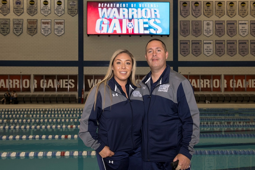 Medically retired Navy Petty Officer 3rd Class Anthony Diele and his wife, Carolina, pose for a photo by the 2018 Defense Department Warrior Games competition pool at the U.S. Air Force Academy in Colorado Springs, Colo. June 4, 2018. DoD photo by EJ Hersom