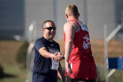 Medically retired Navy Petty Officer 3rd Class Anthony Dieli is congratulated by Marine Corps veteran Sgt. Robert Jones after they ran a 400-meter race during the 2018 Defense Department Warrior Games at the U.S. Air Force Academy in Colorado Springs, Colo., June 2, 2018. Established in 2010, the annual Warrior Games introduce wounded, ill and injured service members to adaptive sports as a way to enhance their recovery and rehabilitation. DoD photo by Roger L. Wollenberg