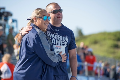 Medically retired Navy Petty Officer 3rd Class Anthony Dieli is congratulated by his wife, Carolina, after running in a 400-meter race during the 2018 Defense Department Warrior Games at the U.S. Air Force Academy in Colorado Springs, Colo., June 2, 2018. DoD photo by Roger L. Wollenberg