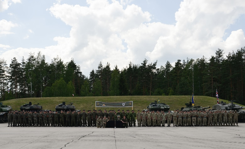 Tank platoons, from eight NATO and partner nations pose together for a photo