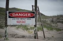 Danger signs stand along the border of Browns Island to warn beach goers not to walk into the impact area.
