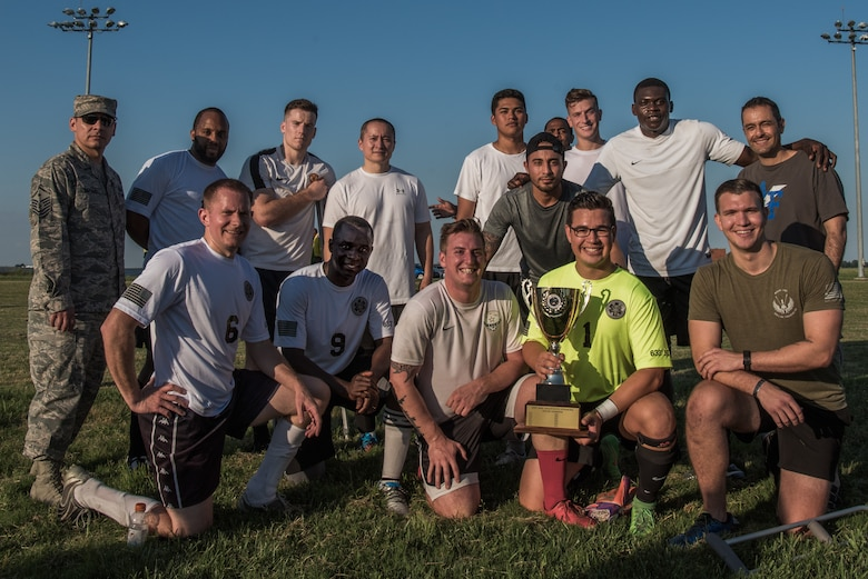 The 633rd Medical Group soccer team poses for a photo with the trophy after winning the Intramural Soccer Championship at Joint Base Langley-Eustis, Virginia, June 4, 2018.