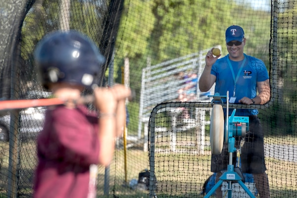 Air Force Capt. Joshua Gradaille shows a practice ball to one of his players before putting it in a pitching machine at Eglin Air Force Base, Fla., May 10, 2018. Gradaille, the executive officer of the base's 33rd Fighter Wing, enrolled his son in baseball when he was five years old to instill the many life lessons he feels team sports offer a child. Air Force photo by Staff Sgt. Peter Thompson
