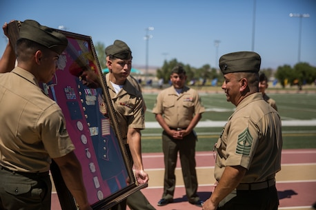 Master Gunnery Sgt. Joseph Lopez, supply chain administration and operations specialist, Headquarters Battalion, is presented a parting gift during his retirement ceremony at Felix Field aboard the Marine Corps Air Ground Combat Center, Twentynine Palms, Calif., June 1, 2018. Lopez is retiring after 30 years of faithful service to country and Corps. (U.S. Marine Corps photo by Lance Cpl. Isaac Cantrell)