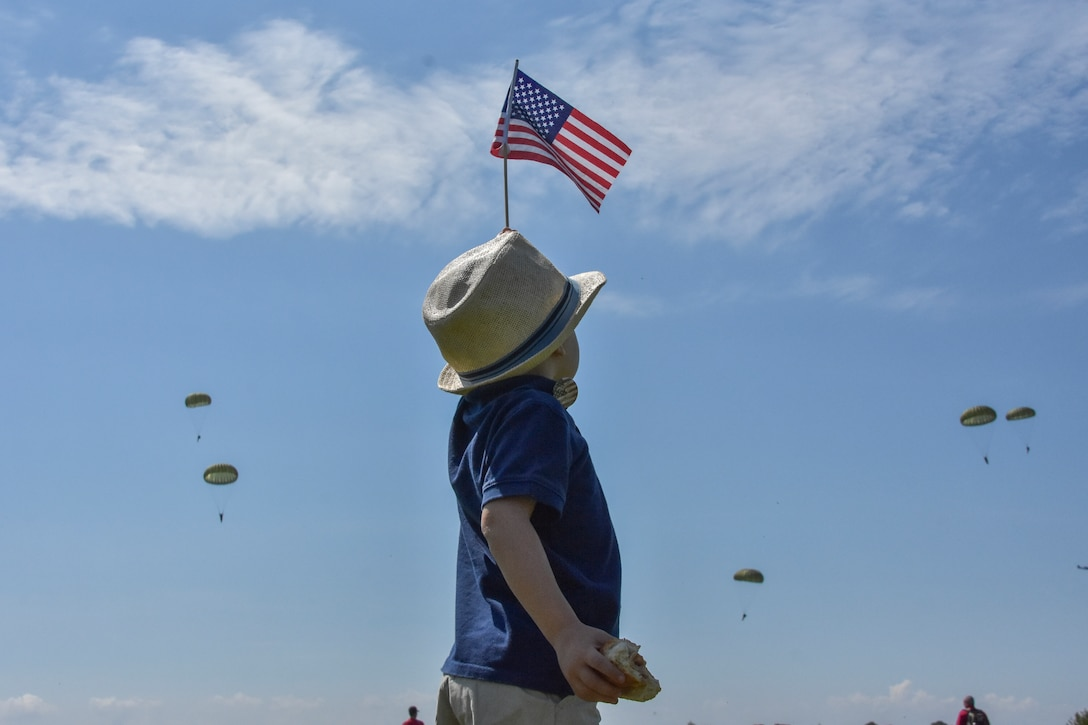 A young boy dressed in a fedora and waving an American flag welcomes paratroopers as they jump into Sainte-Mere-Eglise, France.