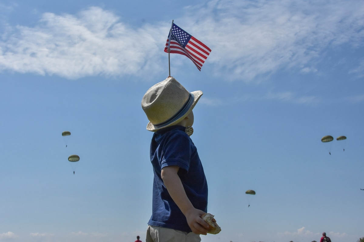 A young boy dressed in a fedora waves an American flag as paratroopers descend in a blue sky.