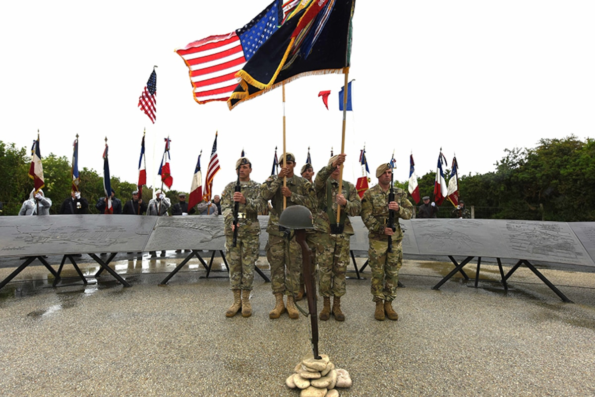 Soldiers hold flags for a ceremony.