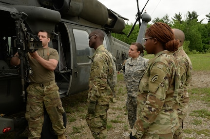 New York Army National Guard Spc. Adam Proctor, assigned to Echo Company, of 3rd Battalion, 142nd Aviation, instructs Soldiers on how to remove empty shells from the brass bag on an M240, on Fort Drum, N.Y., June 2, 2018. Proctor and his company were conducting Aerial Gunnery training to prepare for the National Training Center.