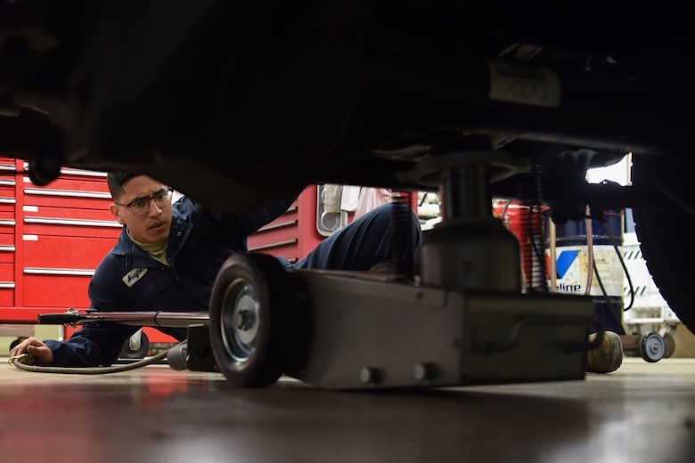 Airman 1st Class Jacobo Abeytia, 30th Logistics Readiness Squadron vehicle maintenance apprentice, places a jack underneath a vehicle during a routine tire change, May 29, 2018, at Vandenberg Air Force Base, Calif. Abeytia lifted the vehicle to begin the tire change. (U.S. Air Force photo by Airman Aubree Milks/Released)