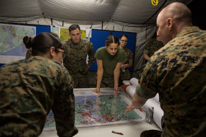 U.S. Marines with 2nd Radio Battalion, II Marine Expeditionary Force Information Group, examine and discuss maps during classes throughout Command Post Exercise (CPX) at Camp Lejeune, N.C., May 22, 2018. 2nd Radio Battalion conducted the CPX to evaluate and improve their communication capabilities in preparation for an upcoming Mission Rehearsal Exercise. (U.S. Marine Corps photo by Lance Cpl. Tiana Boyd)