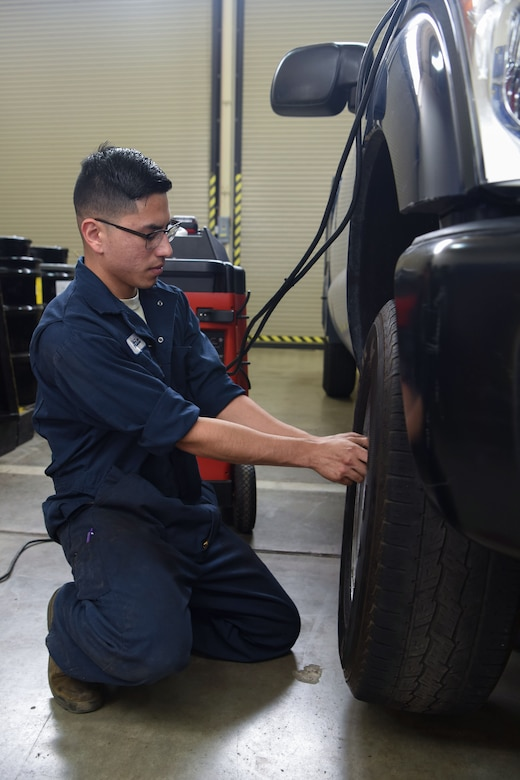 Airman 1st Class Jacobo Abeytia, 30th Logistics Readiness Squadron vehicle maintenance apprentice, places a tire on a vehicle during a routine tire change, May 29, 2018 at Vandenberg Air Force Base, Calif. A vehicle maintenance apprentice practices where an automobile is serviced on a regular basis to prevent a major breakdown or the need for major repair. (U.S. Air Force photo by Airman Aubree Milks/Released)